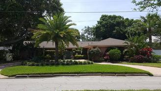 Front of a home with beautiful scenery. Palm trees trimmed, bushes and flower trimmed and grass cut